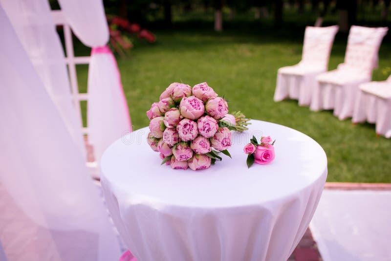 Un bello mazzo di nozze delle rose della peonia, le bugie su una tavola bianca, tutto è pronto per la cerimonia di nozze, bello r fotografia stock