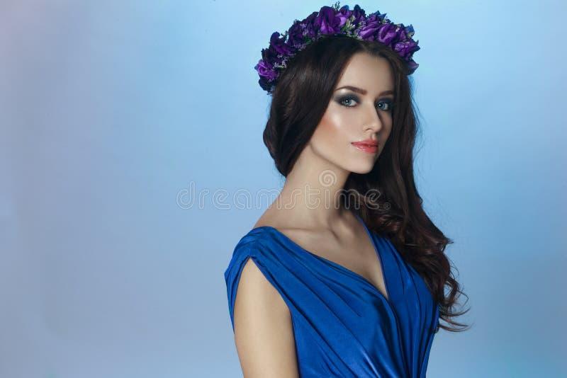 Un bello modello castana con compone e capelli e corona lunghi ricci con i fiori delle viole sulla sua testa fotografia stock libera da diritti