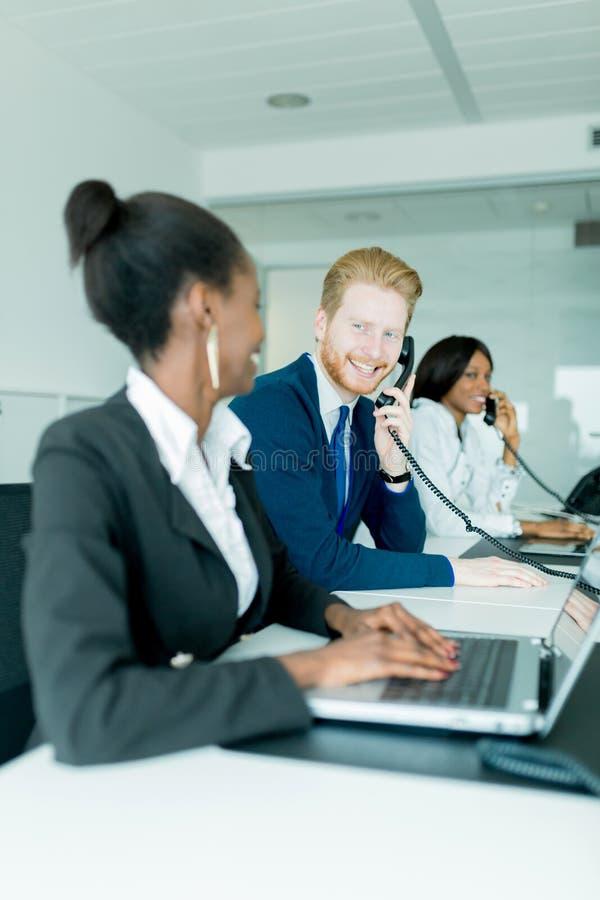Un bello, nero, giovane donna che lavora ad una call center in una o fotografia stock libera da diritti