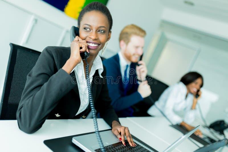 Un bello, nero, giovane donna che lavora ad una call center in una o fotografie stock libere da diritti