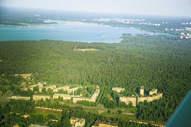 Un bello paesaggio aereo di Riga e di area che guardano da una piccola finestra piana Riga, Lettonia, Europa nell'estate Volo aut fotografia stock