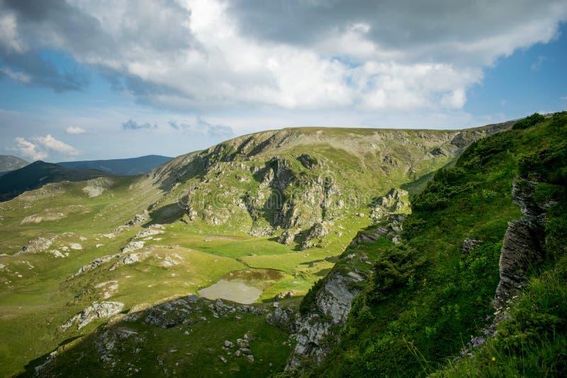 Un bello paesaggio della montagna Un drammatico, cielo blu con molte nuvole Le altezze delle montagne coperte di erba verde e fotografie stock