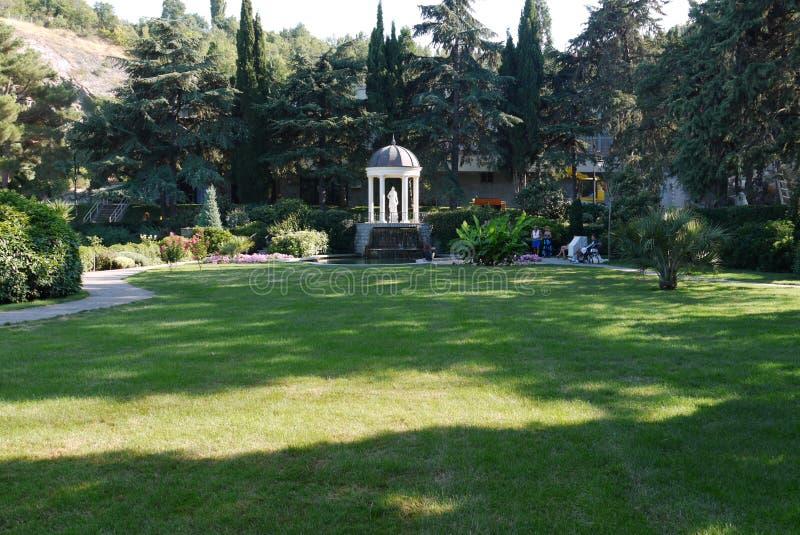 Un bello parco con un prato inglese verde con i colori luminosi dei cespugli tagliati e di una statua bianca diritta in una torre fotografie stock
