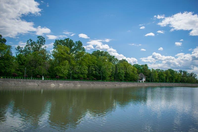 Un bello parco sulla riva di un lago, di una foresta verde meravigliosa e di vecchia casa fotografia stock