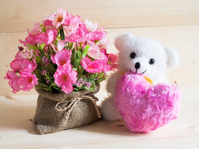 Un bello regalo con l'orso adorabile e fiori piacevoli su fondo di legno fotografia stock