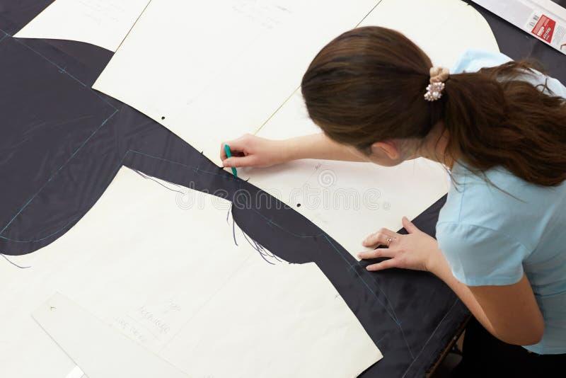 Un bello sarto della ragazza che lavora con un materiale di taglio dentro fotografie stock