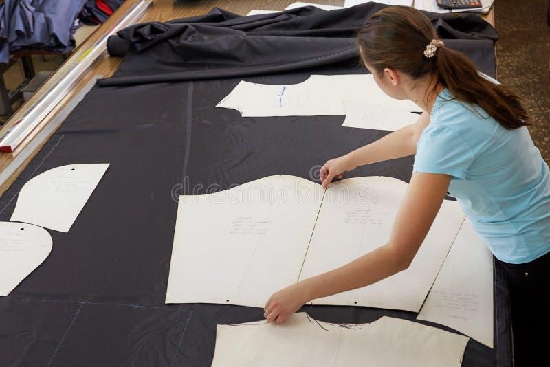 Un bello sarto della ragazza che lavora con un materiale di taglio dentro immagini stock