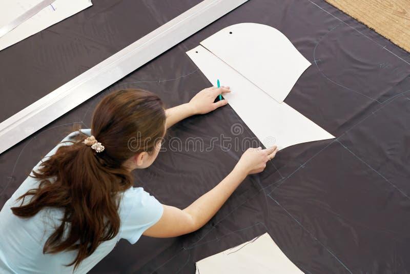 Un bello sarto della ragazza che lavora con un materiale di taglio dentro fotografia stock