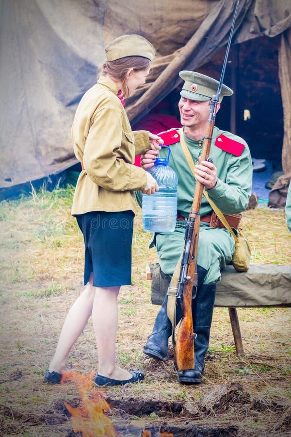 Un bello soldato della ragazza in una tunica ha introdotto l'acqua dolce nelle bottiglie di un soldato con un fucile fotografia stock libera da diritti