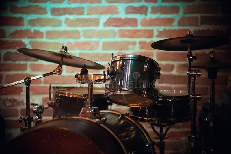 Un bello tamburo sta contro un muro di mattoni in una barra di jazz fotografia stock libera da diritti