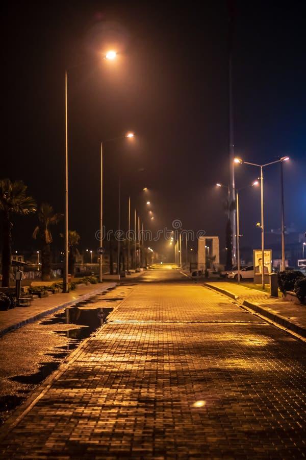 Un bello tiro da una strada della costa - strada di pietra bagnata nell'ambito delle luci della città immagini stock