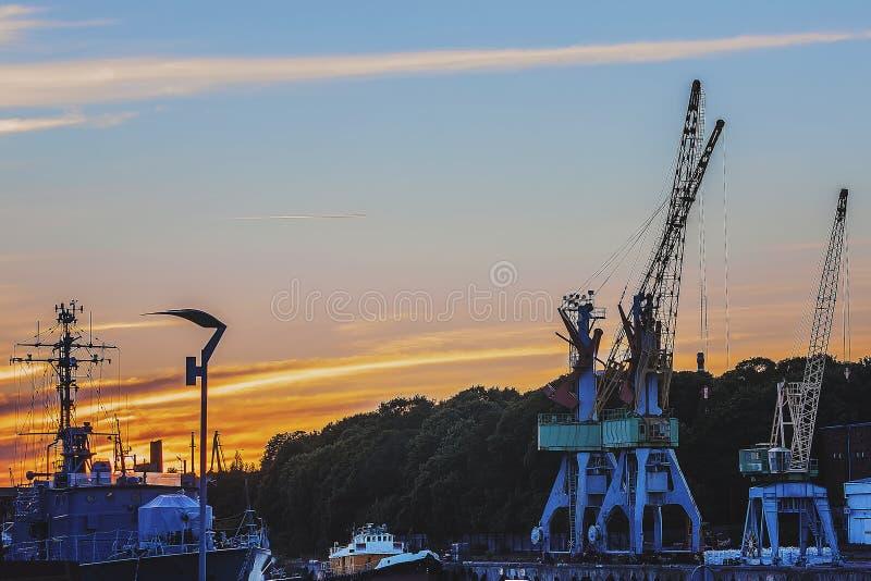 Un bello tramonto sopra le navi del porto della Lettonia fotografia stock