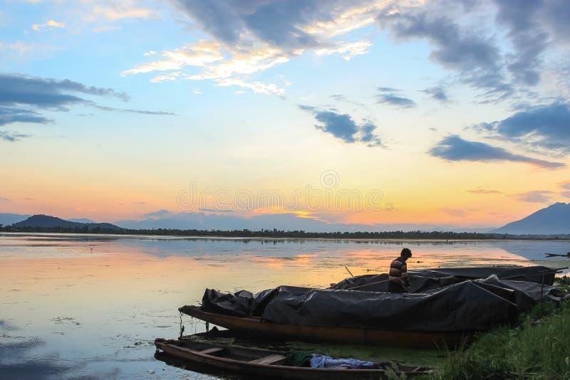 Un bello tramonto su Dal Lake nel Kashmir Barche dei pescatori parcheggiati sulle banche del lago immagine stock