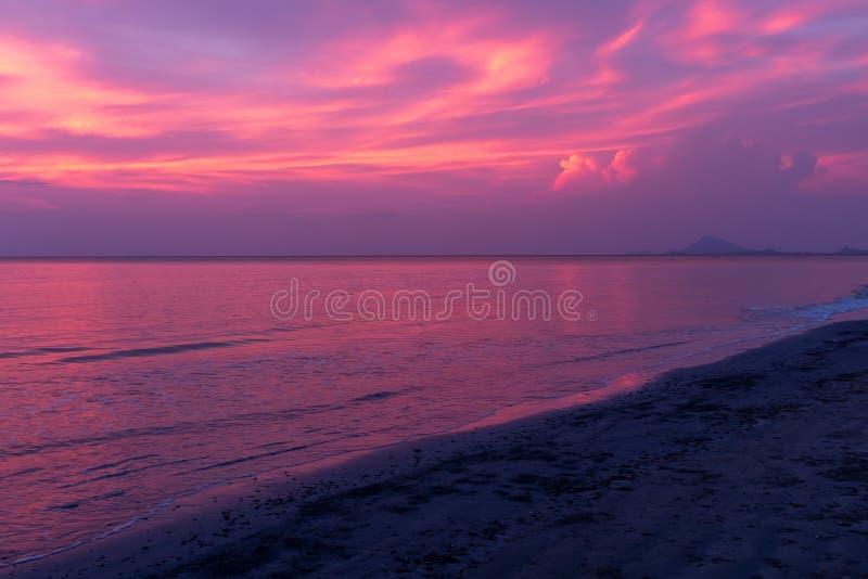 Un bello tramonto su una spiaggia in Koh Lanta, Tailandia, il cielo in fiamme con le porpore ed i blu riflessi nell'oceano immagine stock