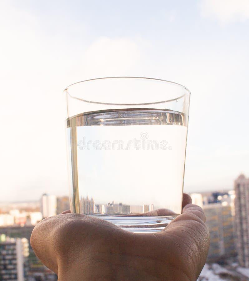 Un bicchiere d'acqua pulito disponibile sul fondo del cielo blu immagini stock libere da diritti
