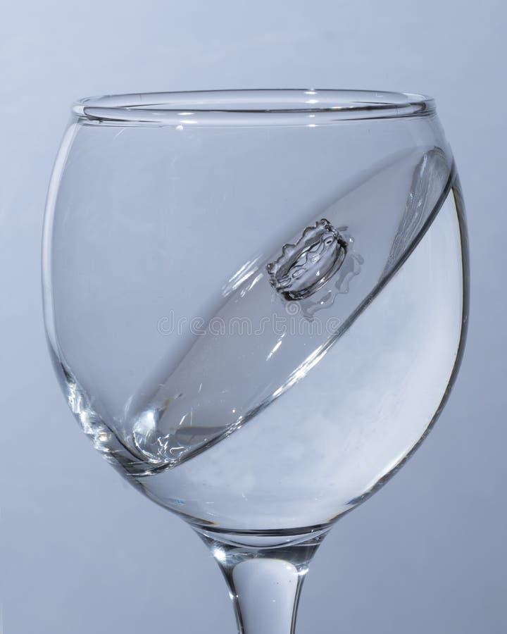 Un bicchiere d'acqua, una goccia caduta immagini stock libere da diritti