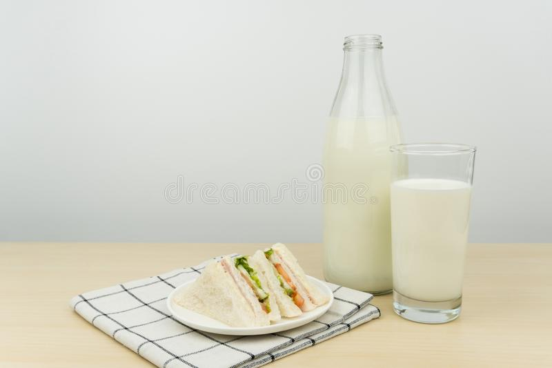 Un bicchiere di latte con la bottiglia per il latte ed i panini di club fotografie stock