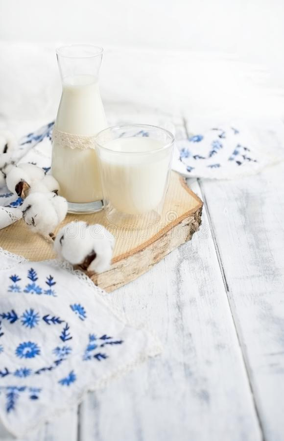 Un bicchiere di latte e una bottiglia di latte Un ramo del cotone e un asciugamano ricamati con i fiori blu Fondo bianco e spazio fotografia stock libera da diritti
