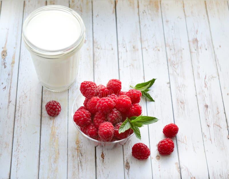Un bicchiere di latte ed i lamponi freschi con la menta su un fondo bianco Nutrizione sana e adeguata Dieta Frutta Dessert fotografie stock libere da diritti