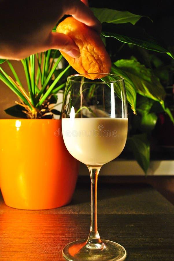 Un bicchiere di latte su una tavola alla luce di sera fotografie stock