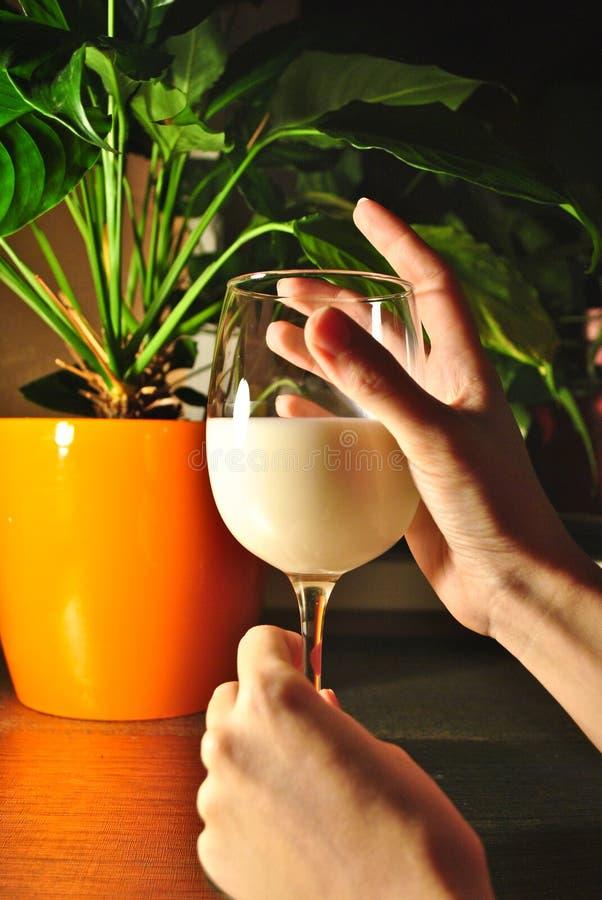 Un bicchiere di latte su una tavola alla luce di sera fotografia stock libera da diritti