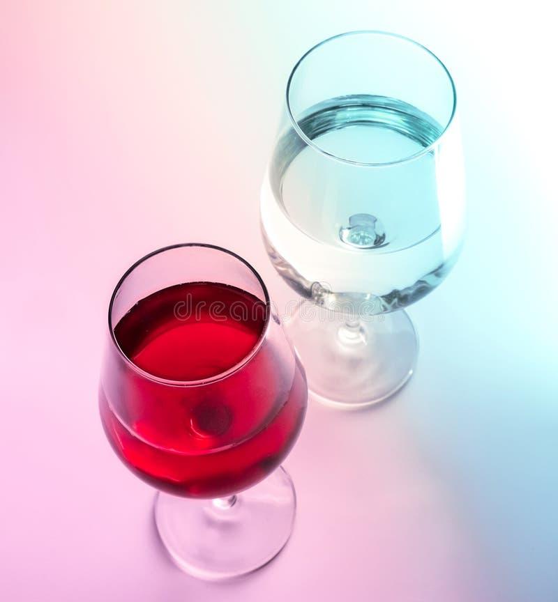 Un bicchiere di vino e un bicchiere d'acqua Rosa e tonalità blu Primo piano immagini stock