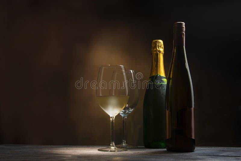 Un bicchiere di vino e un vetro di vino vuoto, accompagnati da una bottiglia aperta di vino e da una bottiglia di champagne che n fotografia stock libera da diritti