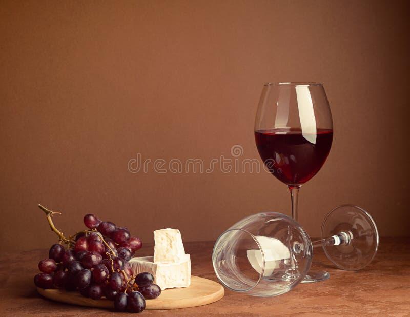 Un bicchiere di vino un mazzo di fondo scuro della fetta del formaggio dell'uva rossa Copi lo spazio Buio di stile di natura mort immagine stock