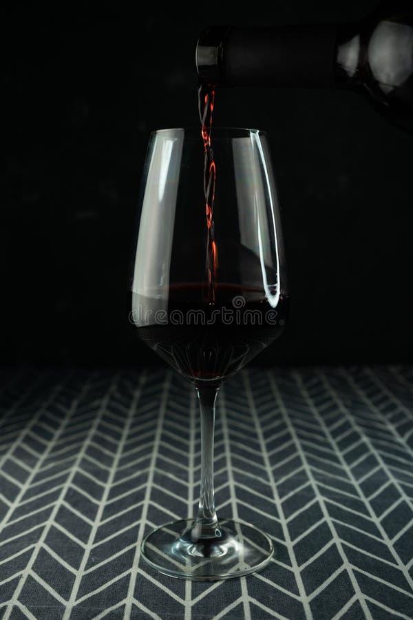 un bicchiere di vino rosso con una bevanda versante immagine stock libera da diritti