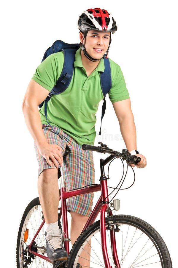 Un bicyclist sonriente joven que presenta en una bicicleta fotos de archivo