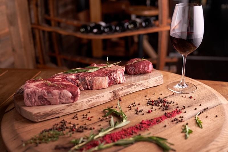 Un bifteck frais et chevronné de Ribeye sur une planche à découper avec le poivre, romarin pr?s d'un verre de vin rouge photographie stock libre de droits