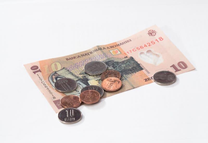 Un billet de banque en valeur 10 le Roumain Lei avec plusieurs pièces de monnaie en valeur 10 et 5 le Roumain Bani d'isolement su photographie stock