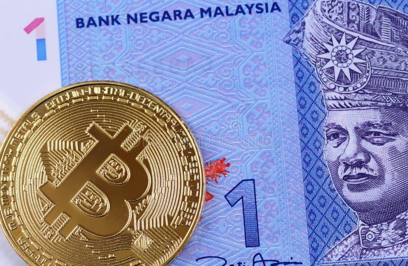 Un un billet de banque malaisien de ringgit avec un bitcoin d'or photos stock