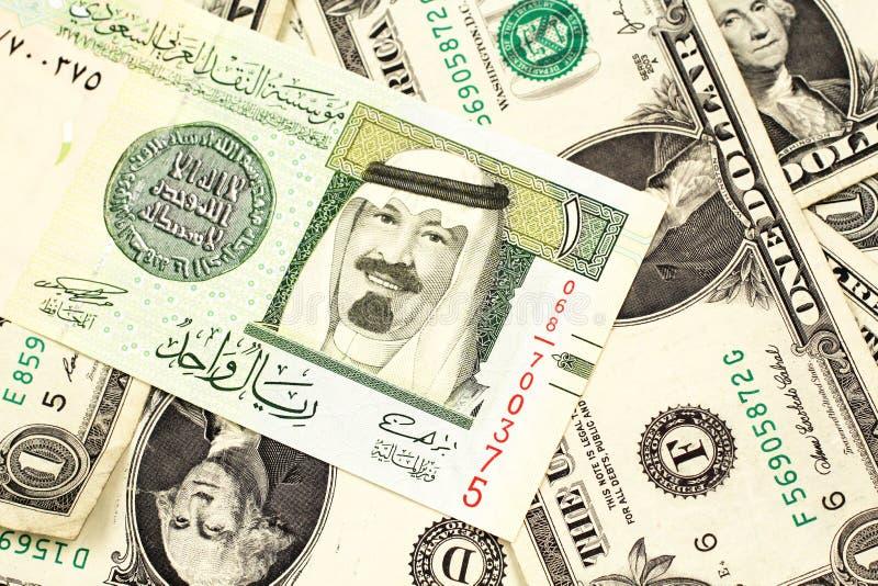 Un un billete de banco de Arabia Saudita del riyal en una cama de los billetes de dólar del americano uno imagen de archivo