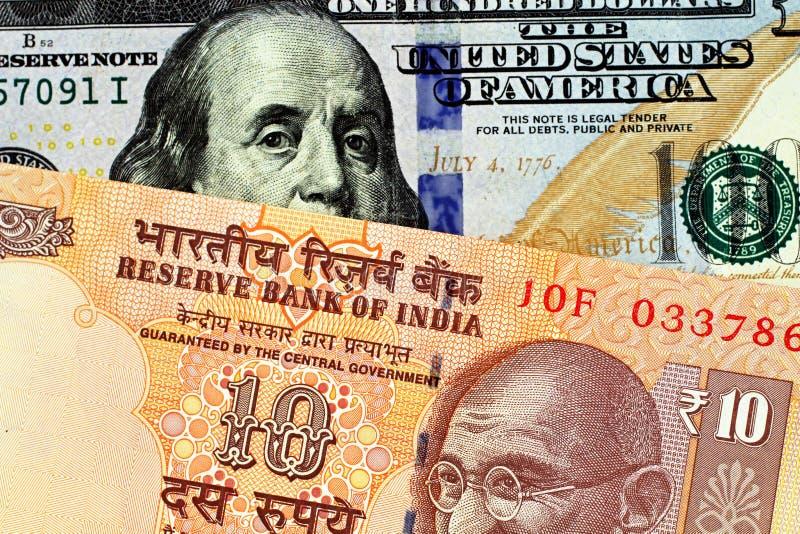 Un billete de banco indio de diez rupias con cientos billetes de dólar americano imagen de archivo libre de regalías