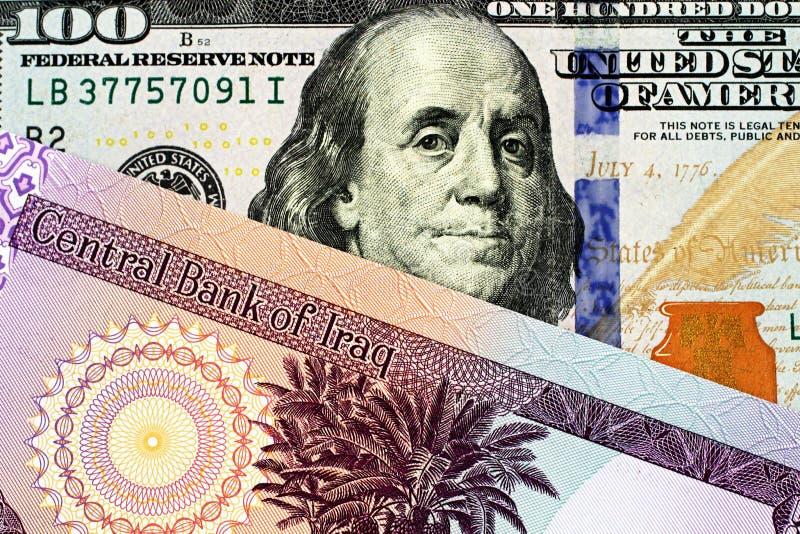Un billete de banco iraquí de cincuenta dinares con cientos billetes de dólar americano foto de archivo