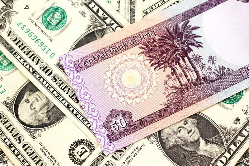 Un billete de banco iraquí de cincuenta dinares con los billetes de dólar del americano uno imagen de archivo libre de regalías