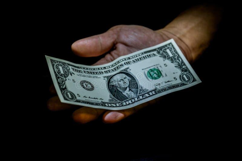 Un billete de dólar en la mano de una persona aislada en negro foto de archivo
