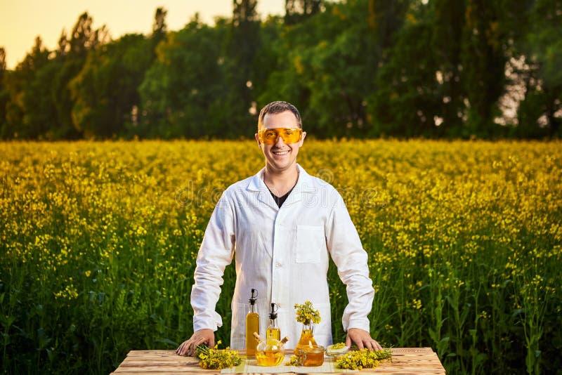 Un biologiste ou un agronome de jeune homme examine la qualité d'huile de graine de colza sur un champ de viol Concept d'agro-ind image stock