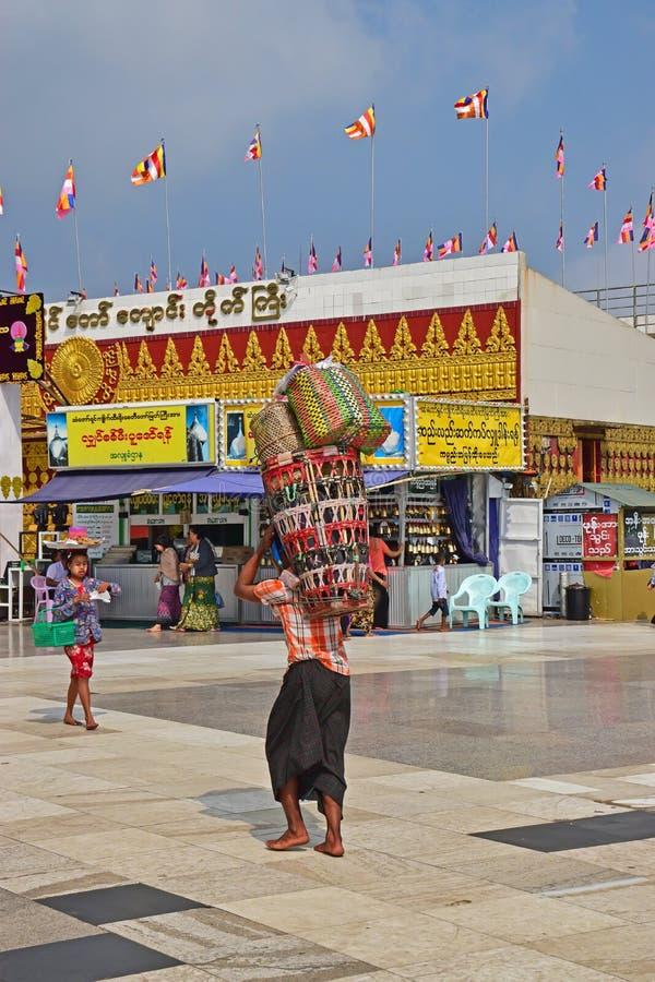 Un birmano che porta i canestri pesanti colourful sulla parte posteriore con più canestri impilati sulla cima fotografie stock libere da diritti