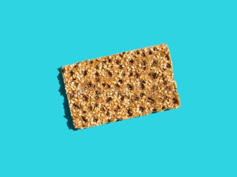 Un biscote curruscante entero del grano del centeno escandinavo con las semillas de sésamo en fondo azul sólido Sombras duras dif foto de archivo libre de regalías