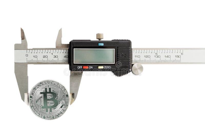Un bitcoin de la moneda medido con un calibrador Aislado en blanco fotos de archivo libres de regalías