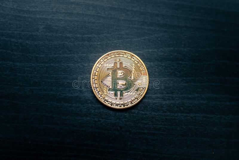 Un bitcoin físico en el medio de un fondo de madera oscuro imagenes de archivo