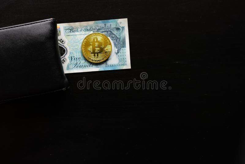 Un bitcoin físico se sienta encima de libras inglesas al lado de una cartera imagen de archivo libre de regalías