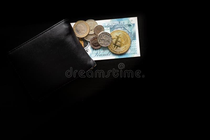 Un bitcoin físico se sienta encima de libras inglesas al lado de una cartera imagenes de archivo