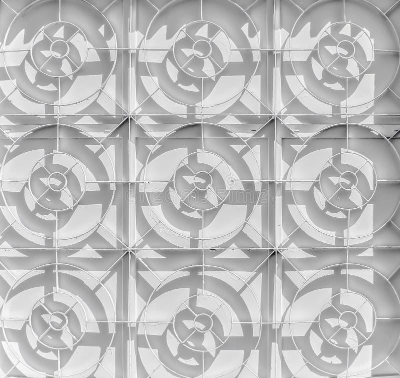 Un blanco pintó enrejado en una ventana ciega de la planta foto de archivo libre de regalías