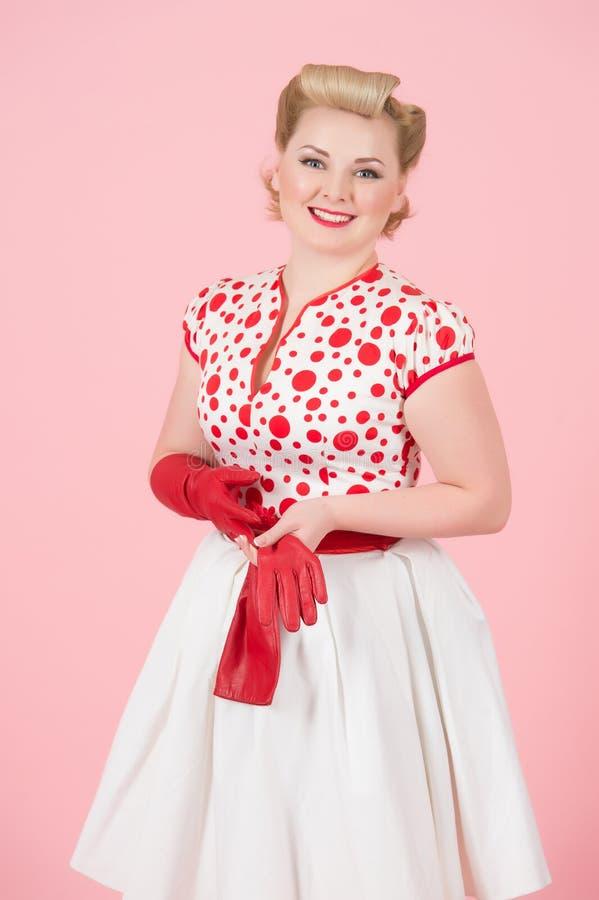 Un blonde de la felicidad de la muchacha con los guantes largos rojos en fondo del rosa en colores pastel Mujer bonita de los riz imagenes de archivo