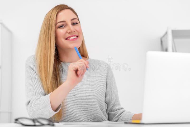 Un blonde muy hermoso se está sentando en una tabla con un ordenador portátil y una pluma en su mano Mujer atractiva joven en ofi imagen de archivo