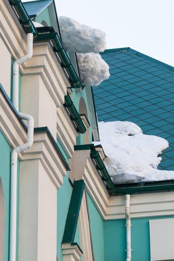 Un bloque enorme de la nieve cuelga del tejado sobre la entrada al edificio imagen de archivo libre de regalías