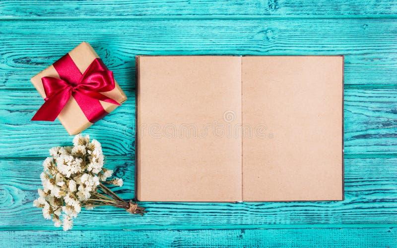 Un boîte-cadeau avec un ruban de satin et un livre ouvert avec les pages vides sur un fond bleu Milieux et textures Copiez l'espa image stock